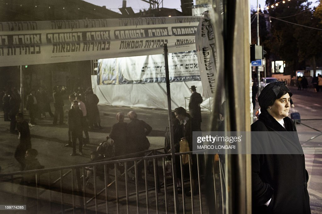A woman looks on as Ultra Orthodox Jews belonging to the Satmar Hasidic group headed by Satmar Rebbe of Williamsburg, Rabbi Zalman Leib Teitelbaum, gather for an anti-election rally in the conservative Mea Shearim neighbourhood of Jerusalem on January 20, 2013, two days before nationwide voting for the general election gets underway on January 22.
