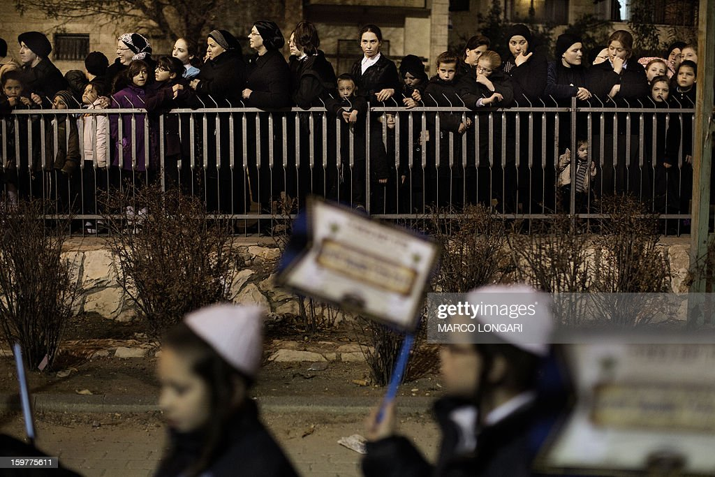 Woman looks on as Ultra Orthodox Jews belonging to the Satmar Hasidic group headed by Satmar Rebbe of Williamsburg, Rabbi Zalman Leib Teitelbaum, gather in the conservative Mea Shearim neighbourhood of Jerusalem on January 20, 2013, two days before nationwide voting for the general election gets underway on January 22. AFP PHOTO/MARCO LONGARI