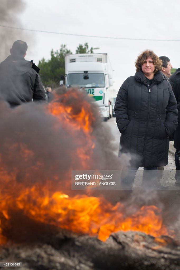 A woman looks on as workers of semiconductor manufacturer LFoundry block the access to the Industrial Zone in Rousset, near Aix-en-Provence, southern France, on December 23, 2013, after trade unions announced that a court had ordered a judicial liquidation of their factory. Over 670 jobs are at risk if the factory closes and approximately 400 workers took part in the protest and blocade of the Rousset industrial zone, as French Minister for Industrial Renewal Arnaud Montebourg prepared to receive a delegation of workers in Paris today. AFP PHOTO / BERTRAND LANGLOIS