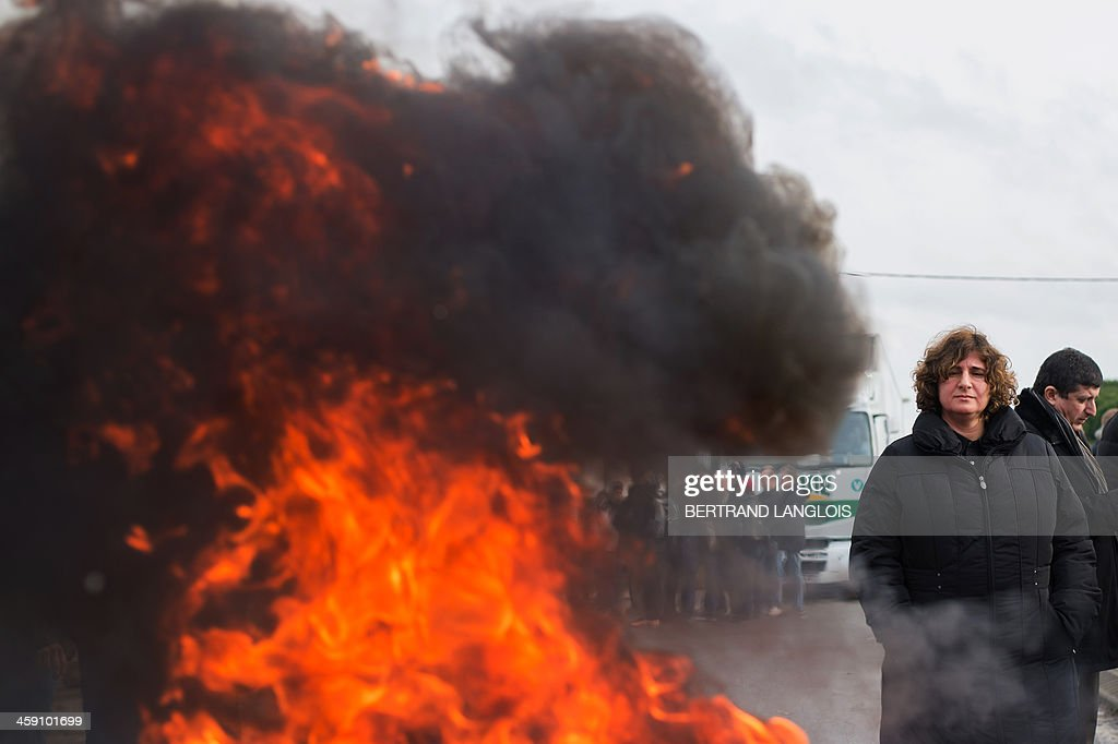 A woman looks on as workers of semiconductor manufacturer LFoundry block the access to the Industrial Zone in Rousset, near Aix-en-Provence, southern France, on December 23, 2013, after trade unions announced that a court had ordered a judicial liquidation of their factory. Over 670 jobs are at risk if the factory closes and approximately 400 workers took part in the protest and blocade of the Rousset industrial zone, as French Minister for Industrial Renewal Arnaud Montebourg prepared to receive a delegation of workers in Paris today.