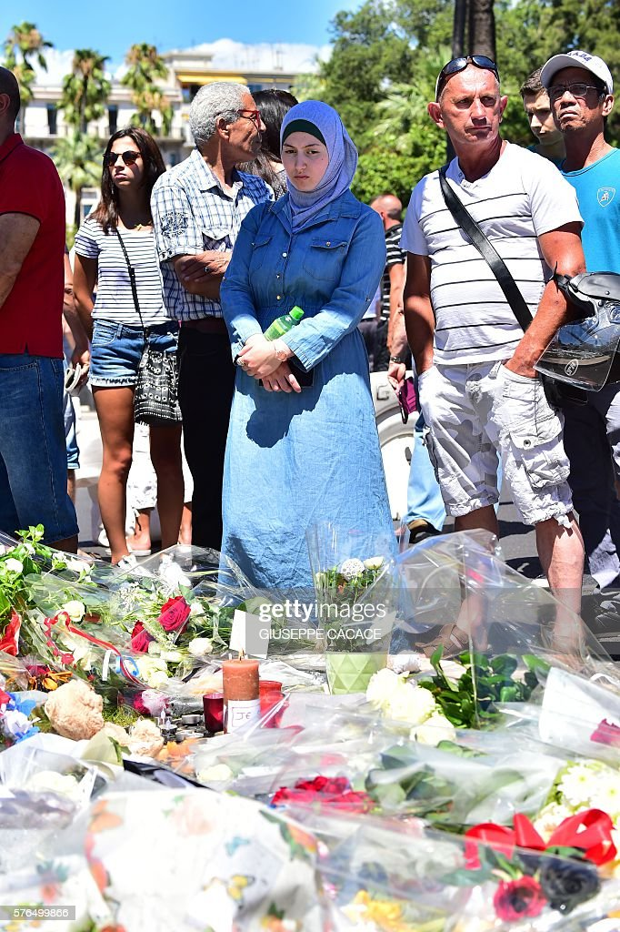 A woman looks on at a make-shift memorial site on July 15, 2016 in Nice, created in tribute to victims of the deadly Bastille Day attack. A Tunisian-born man zigzagged a truck through a crowd celebrating Bastille Day in the French city of Nice, killing at least 84 and injuring dozens of children in what President Francois Hollande on July 15 called a 'terrorist' attack. / AFP / GIUSEPPE