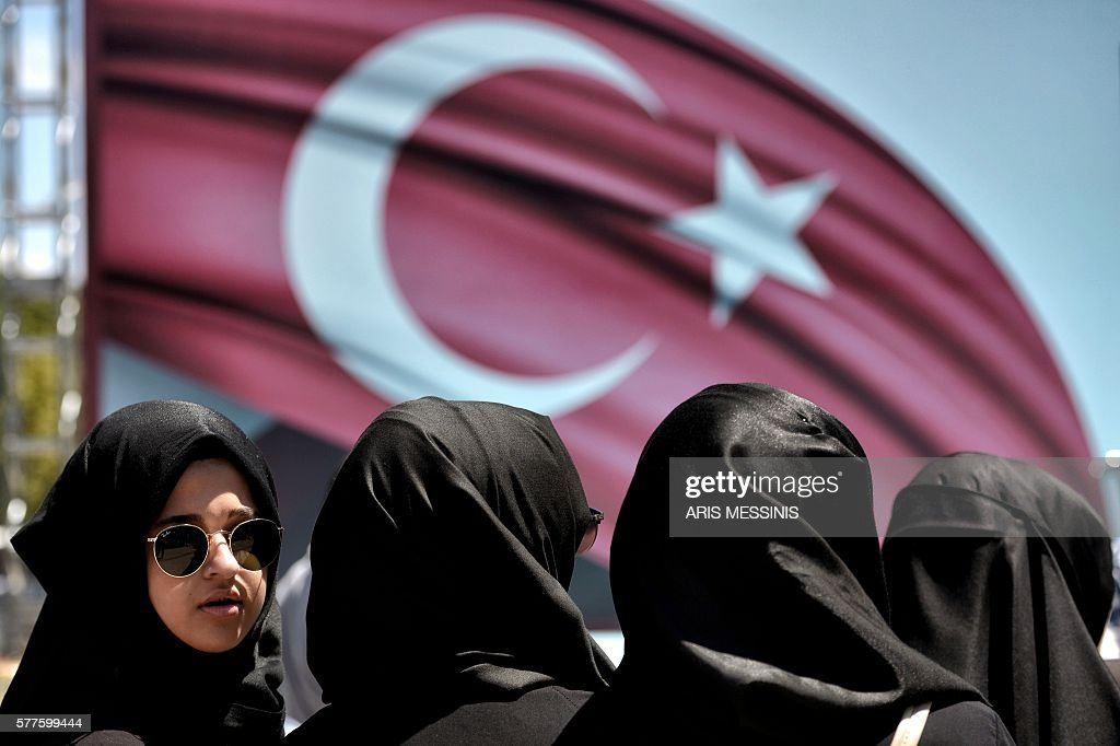 A woman looks on during a demonstration in support of Turkey's President Erdogan (not pictured) at the Sarachane park in Istanbul on July 19, 2016. Turkey has demanded the resignation of 1,577 university deans suspected of being connected with Friday's attempted coup, state-run news agency Anadolu reported July 19. The country's higher education board made the demand for deans at state and private foundation universities to resign, Anadolu said. MESSINIS
