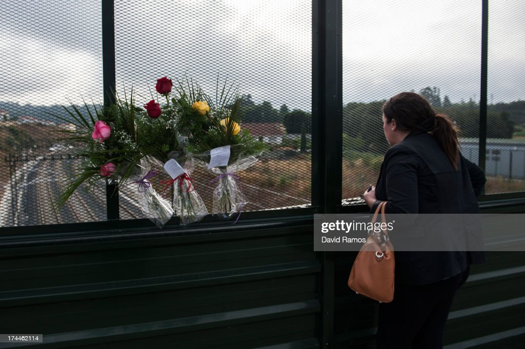A woman looks on from a bridge over the rail next to flowers to remember the victims of a train crash that killed 78 people on July 26, 2013 in Santiago de Compostela, Spain. The crash occurred as the train approached the north-western Spanish city of Santiago de Compostela at 8.40pm on July 24th, at least 78 people have died and a further 131 reported injured. The crash occured on the eve of the Santiago de Compostela Festivities.