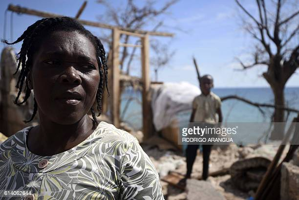 TOPSHOT A woman looks on in her home destroyed by Hurricane Matthew in Port Salut southwest of PortauPrince on October 11 2016 Haiti faces a...