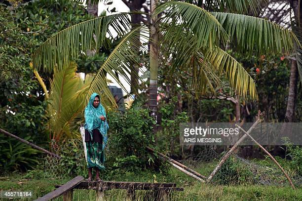 A woman looks on while standing in the yard of her house in the town of Kerema Papua New Guinea on September 7 2014 AFP PHOTO / ARIS MESSINIS