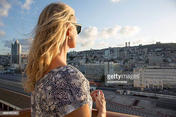 Woman looks out across city scene at sunrise