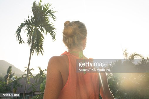 Woman looks out across jungle and village, sunrise : Stock Photo