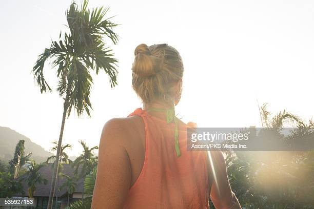 Woman looks out across jungle and village, sunrise