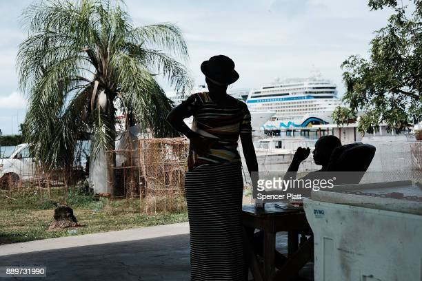 A woman looks out at a cruise ship sitting in the harbor on December 10 2017 in St John's Antiqua While it's sister island Barbuda was nearly...