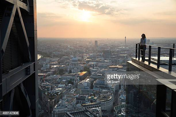 A woman looks out at the London skyline from an upper floor of a newly constructed skyscraper The Leadenhall Building as the sun sets on September 9...