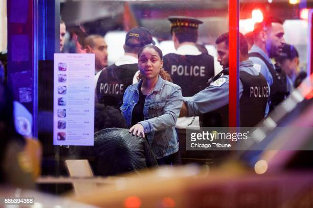 A woman looks out at the scene where three people were shot on Saturday Oct 21 2017 at a Taco Burrito King Restaurant in Chicago Ill