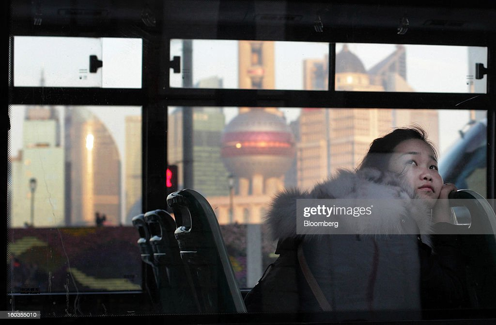 A woman looks out from a bus window as it moves along the Bund while buildings stand in the Lujiazui district in Shanghai, China, on Monday, Jan. 28, 2013. China's economic growth accelerated for the first time in two years as government efforts to revive demand drove a rebound in industrial output, retail sales and the housing market. Photographer: Tomohiro Ohsumi/Bloomberg via Getty Images