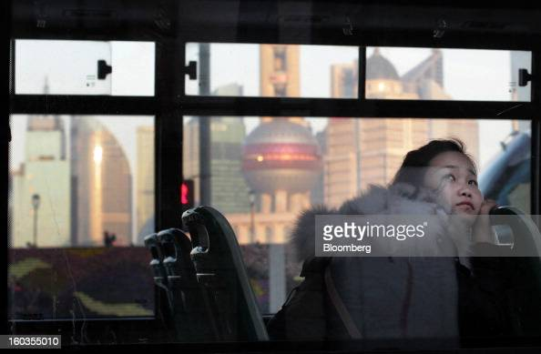A woman looks out from a bus window as it moves along the Bund while buildings stand in the Lujiazui district in Shanghai China on Monday Jan 28 2013...