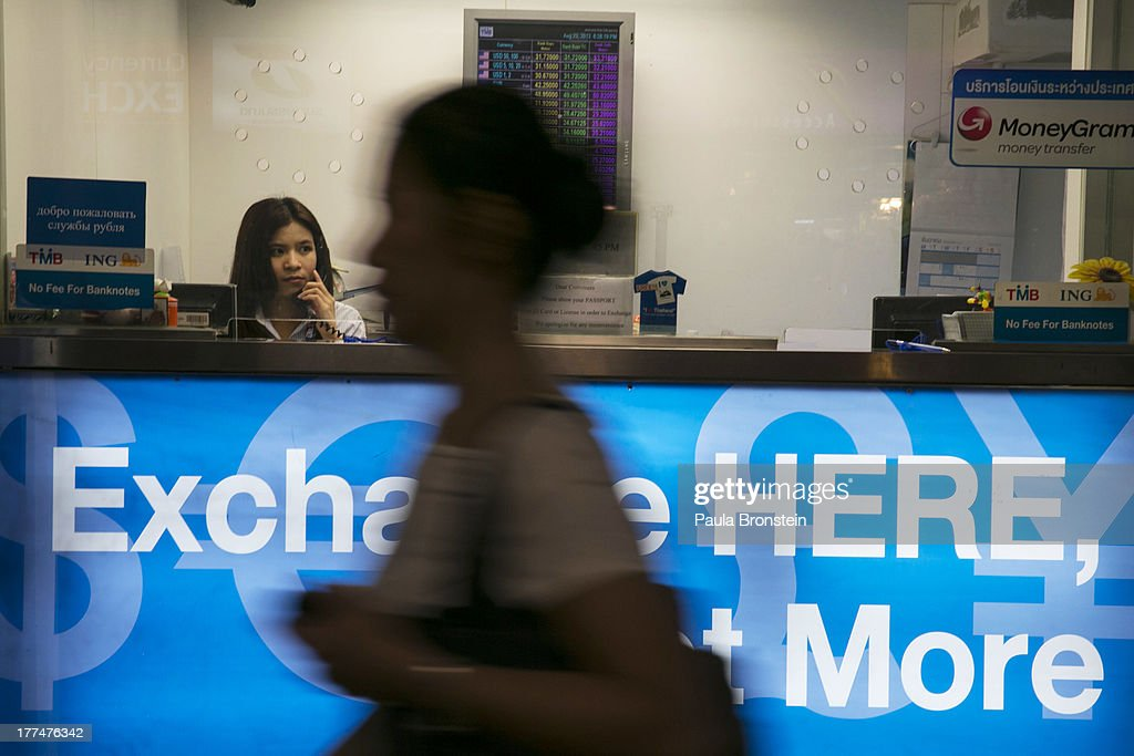 A woman looks out from a money exchange bank kiosk on August 23, 2013 in downtown Bangkok, Thailand. The local currency dropped to its lowest level since August 2010. Against the US dollar the Thai baht fell to 32.09/32.13 dropping about 5% this year.