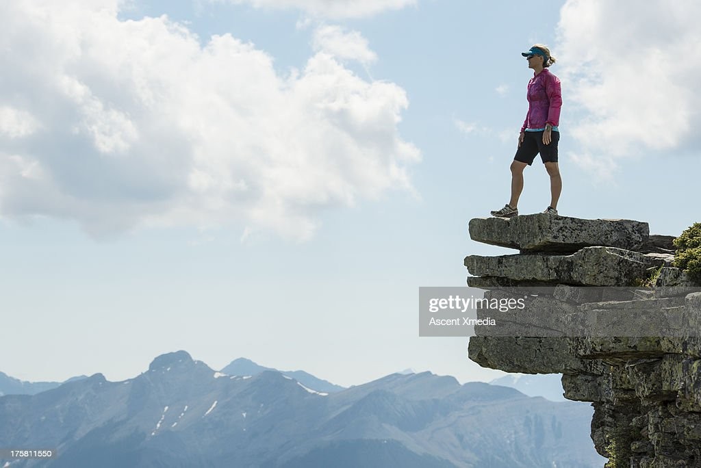 Woman looks out from bluff above mountains
