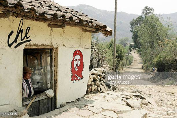 A woman looks out from inside her home which depicts a mural depicting legendary Argentineborn guerrilla leader Ernesto 'Che' Guevara on the wall 03...