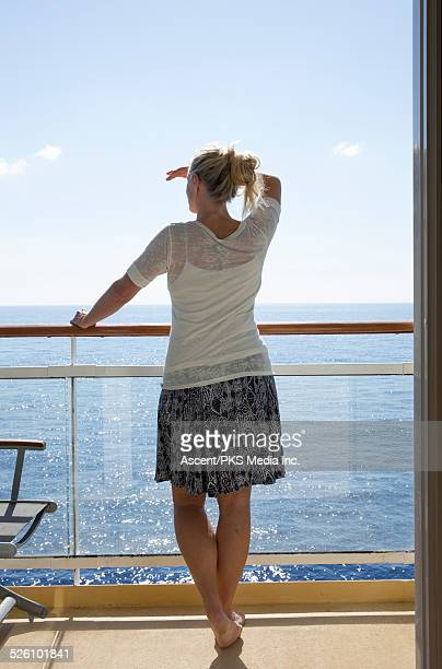 Woman looks out from rail of ship at sea