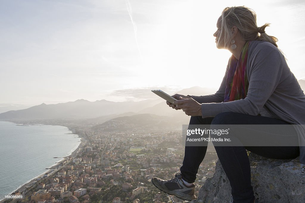 Woman looks out from rock promontory, above sea