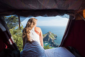 Woman looks out from tent to sea vista below