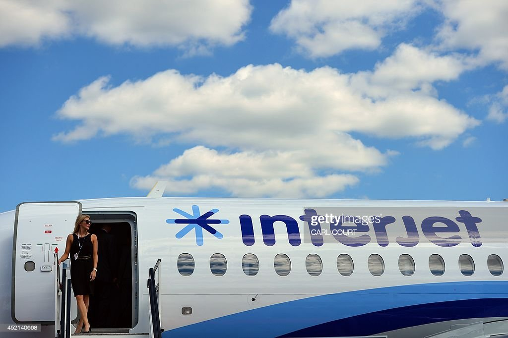 A woman looks out from the steps leading to a Sukhoi Superjet 100 at the Farnborough air show in Hampshire England on July 14 2014 The biennial event...
