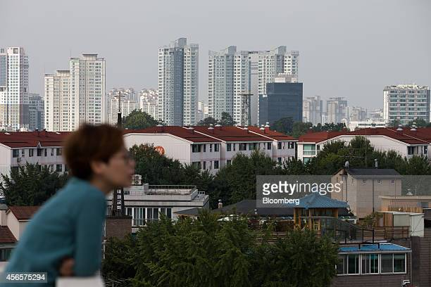 A woman looks out in front of houses and apartment buildings standing in the Yongsan district in Seoul South Korea on Tuesday Sept 30 2014 South...