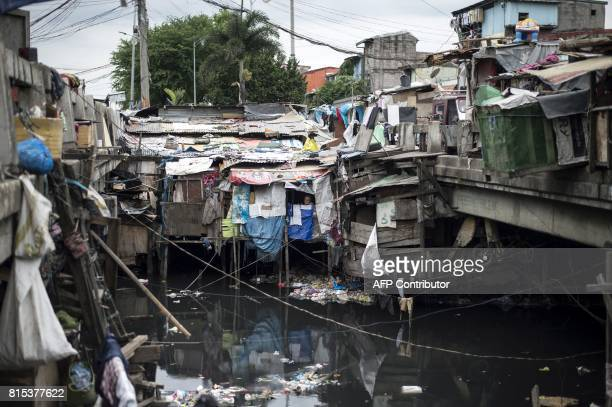 A woman looks out of a window at one of the shanties erected at the Estero de Vitas in Manila on July 16 2017 The Philippine economy has sustained...