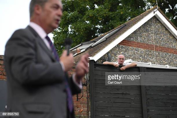 A woman looks out of her skylight and a man looks ovver his fence to watch former UKIP leader Nigel Farage speak as he campaigns ahead of the general...