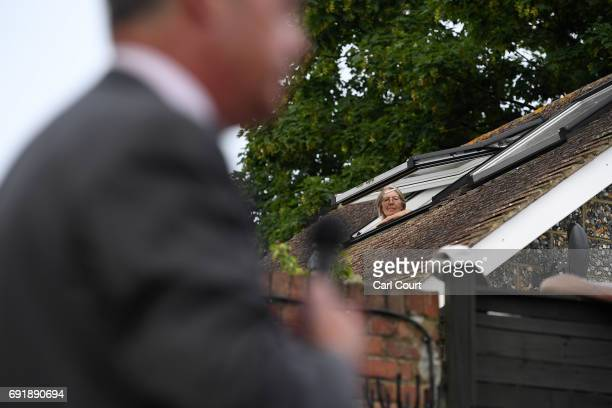 A woman looks out of her skylight to watch former UKIP leader Nigel Farage speak as he campaigns ahead of the general election on June 3 2017 in...