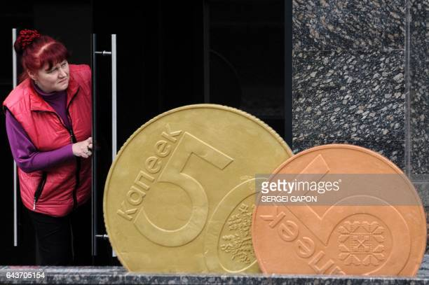 A woman looks out of the door next to a giant Belarusian ruble coin monument near the Ministry of taxesandduties in Minsk on February 22 2017 / AFP /...