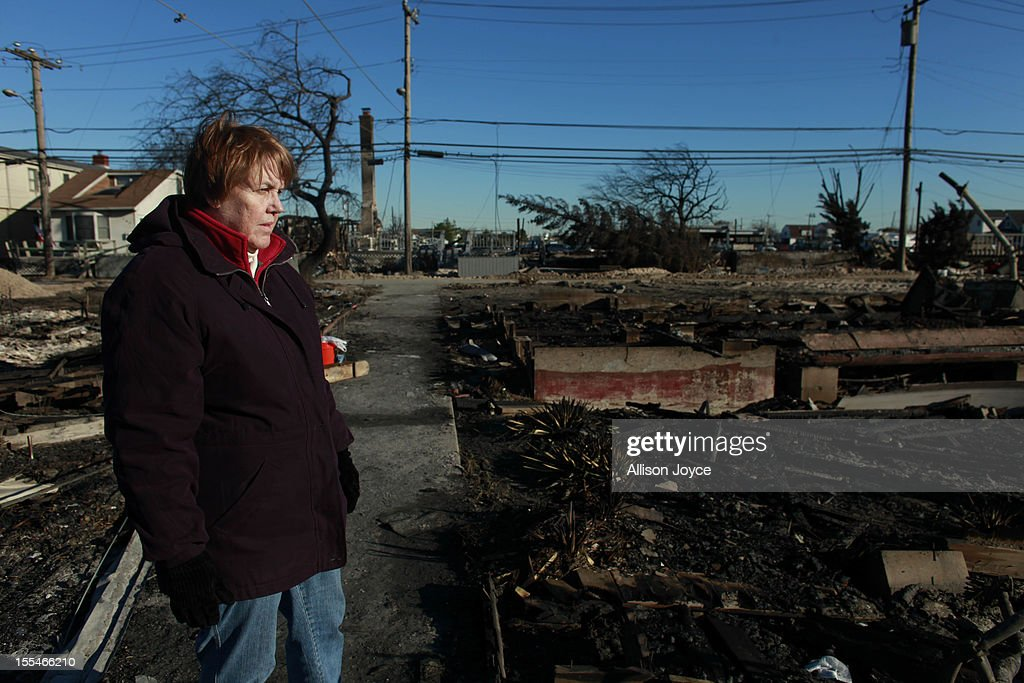 A woman looks out onto a neighborhood damaged by a fire November 4, 2012 in the Breezy Point neighborhood of the Queens borough of New York City. With the death toll currently over 100 and millions of homes and businesses without power, the US east coast is attempting to recover from the effects of floods, fires and power outages brought on by Superstorm Sandy.