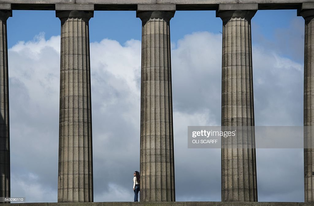 A woman looks out over the city as she stands on the National Monument of Scotland, on Calton Hill in Edinburgh, Scotland on June 27, 2016. British leaders battled to calm markets and the country Monday after its shock vote to leave the EU, while insisting London would be not rushed into a quick divorce. Britain's historic decision to be the first country to leave the 28-nation bloc has fuelled fears of a break-up of the United Kingdom with Scotland eyeing a new independence poll, and created turmoil in the opposition Labour party where leader Jeremy Corbyn is battling an all-out revolt. / AFP / OLI