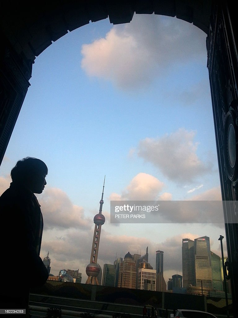 A woman looks out over the Shanghai skyline on February 21, 2013. China is considering a ban on barbecues to help reduce air pollution in built-up areas after heavy smog recently choked large swathes of the country, state media reported today. AFP PHOTO / Peter PARKS