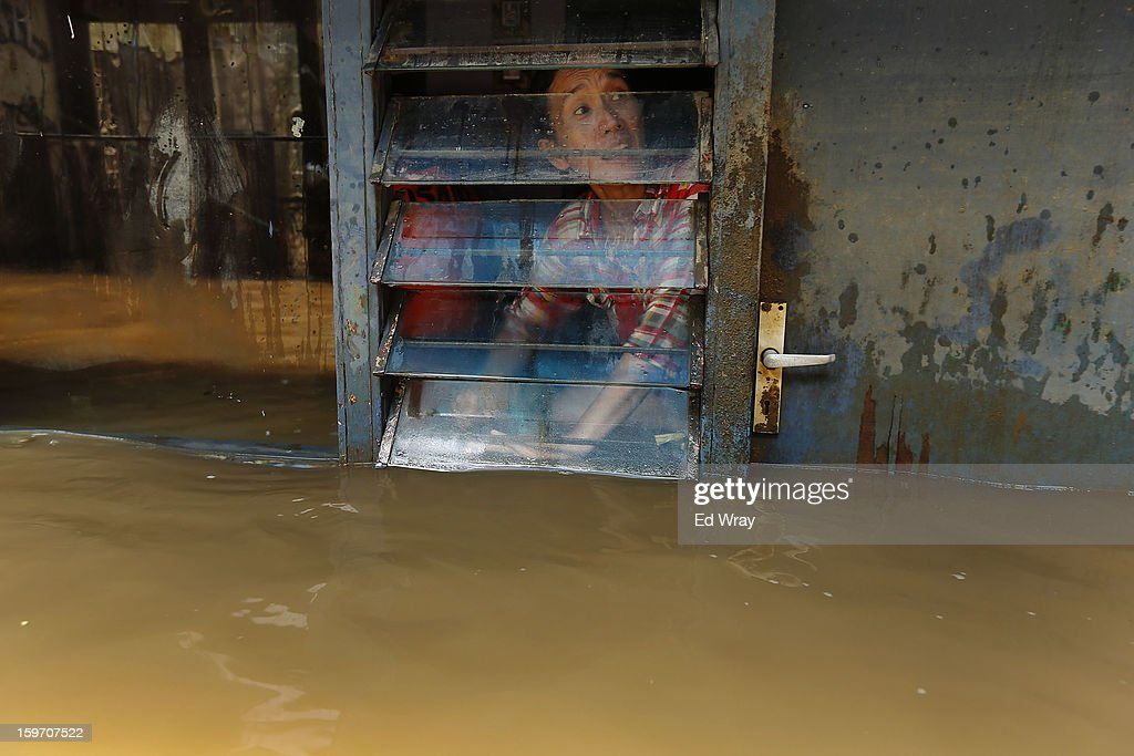 A woman looks out the window of her flooded home January 19, 2013 in Jakarta, Indonesia. Floodwaters receded today after three days of heavy flooding which left thousands of people's homes underwater. According to Indonesian police the death toll has reached 15.