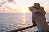 Woman looks out to sea from railing of ship