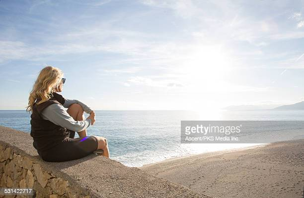 Woman looks out to sea from stone wall perch