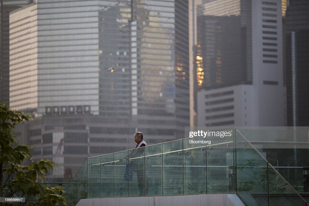 A woman looks out towards the harbor from a viewing deck outside Tamar Park in Hong Kong, China, on Wednesday, Jan. 16, 2013. Hong Kong will maintain property curbs for overseas buyers as it seeks to meet the housing needs of its people, Chief Executive Leung Chun-ying said in his first policy address today. Photographer: Jerome Favre/Bloomberg via Getty Images