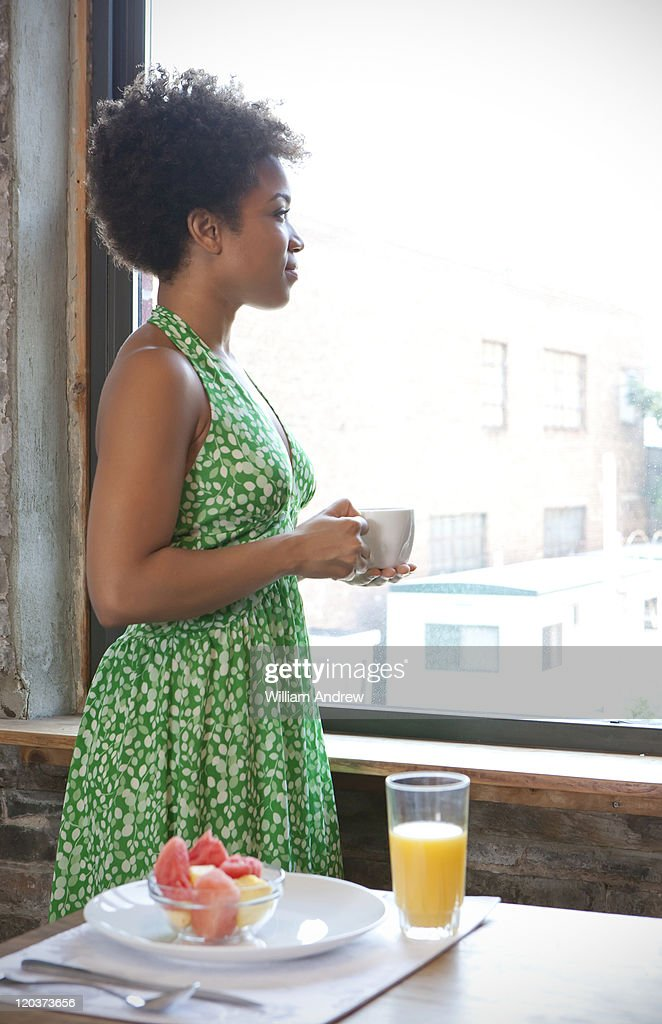 Woman looks out window : Stock Photo