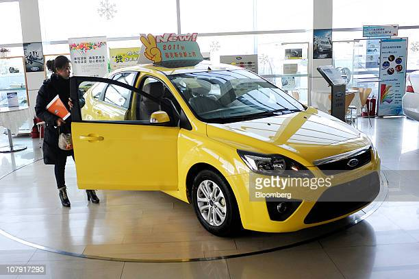 A woman looks over a Ford Motor Co Focus on display at a dealership in Beijing China Friday Jan 7 2011 Ford Motor Co said its vehicle sales in China...