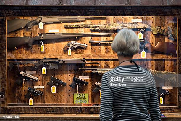A woman looks over the 'Wall of Guns' raffle case during the 144th National Rifle Association Annual Meetings and Exhibits at the Music City Center...