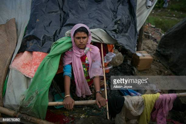 COX'S BAZAR BANGLADESH SEPTEMBER 19 A woman looks through a hole in her house in the Falungkhali Rohingya refugee camp on September 19 2017 in Cox's...