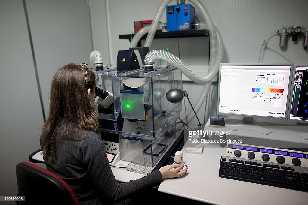 A woman looks through a microscope at the National Biotechnology Centre on February 7, 2013 in Madrid, Spain.