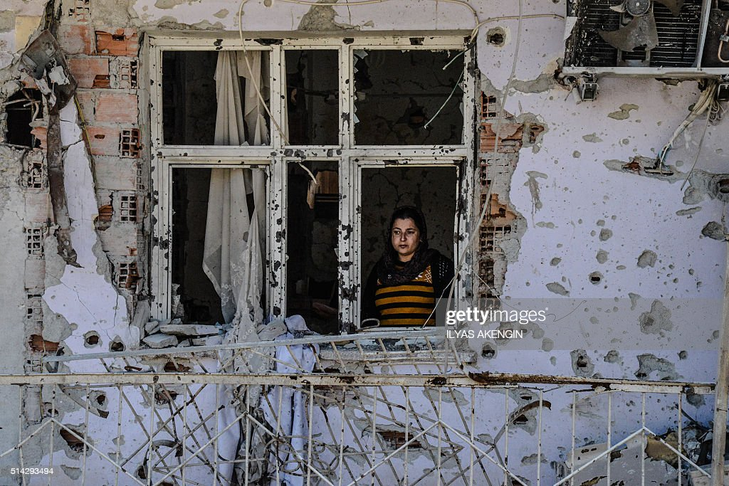 TOPSHOT A woman looks through a window of her ruined house on March 8 2016 during International Women`s day in Cizre district Residents of Cizre in...