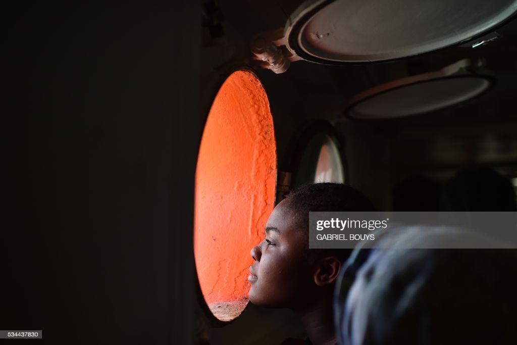 A woman looks through a window of rescue ship 'Aquarius' as more the 380 migrants arrive in the port of Cagliari, Sardinia, on May 26, 2016, two days after being rescued near the Libyan coasts. The Aquarius is a former North Atlantic fisheries protection ship now used by humanitarians SOS Mediterranee and Medecins Sans Frontieres (Doctors without Borders) which patrols to rescue migrants and refugees trying to reach Europe crossing the Mediterranean sea aboard rubber boats or old fishing boat. / AFP / GABRIEL
