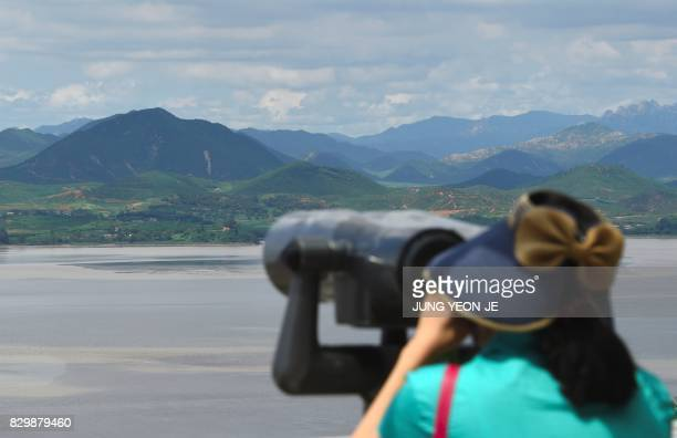 A woman looks through binoculars towards North Korea from a South Korean observation post in Paju near the Demilitarized Zone dividing two Koreas on...