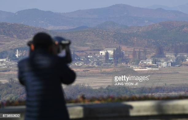 A woman looks through binoculars towards North Korea from a South Korean observation post in Paju near the Demilitarized Zone dividing the two Koreas...