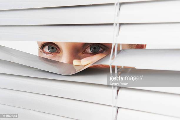 Woman looks through blinds