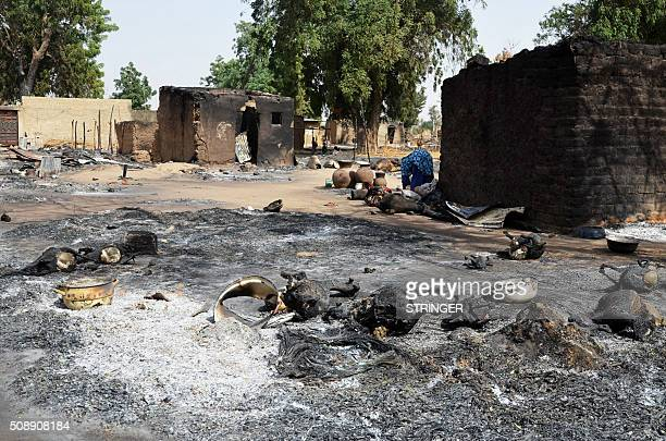 A woman looks through burnt livestocks and litters on the ground caused by Boko Haram Islamists at Mairi village outskirts of Maiduguri capital of...