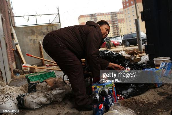 A woman looks through discarded food from a flooded grocery store in the heavily damaged Rockaway neighborhood where a large section of the iconic...
