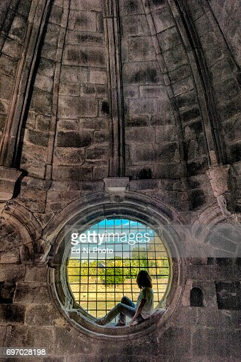 Woman looks through grated circular window : Foto stock