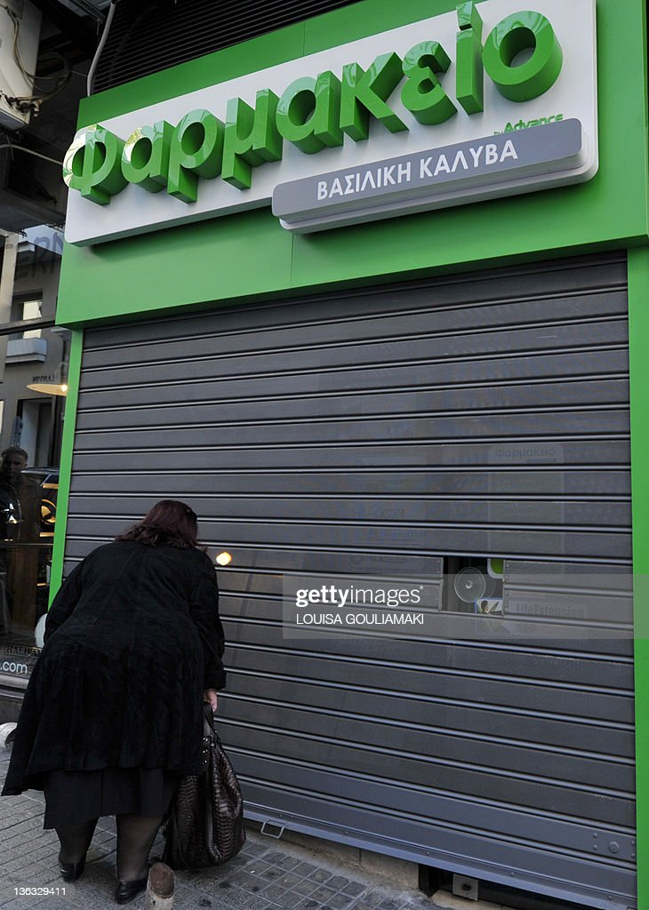 A woman looks through pharmacy shutters in central Athens during a rolling 48hour strike of Greek pharmacists and doctors against reforms on January...